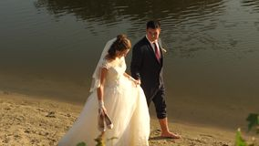 Happy bride and groom walk barefoot in the sand along the riverbank. couple in love goes hand in hand on the beach stock video footage