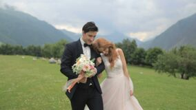 Happy bride and groom are walking along green grass. Groom and bride in beautiful dress walking along green grass against the background of the mountains stock footage