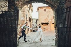 Lovely hugging wedding couple stands before the gates to an old Royalty Free Stock Images