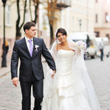 Happy bride and groom walking in an old town Stock Image