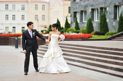 Happy bride and groom walking in an old town Royalty Free Stock Photo