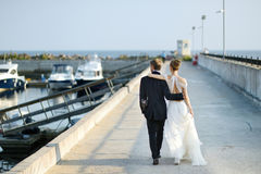 Happy bride and groom walking on pier Royalty Free Stock Photos