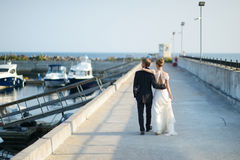 Happy bride and groom walking on pier Royalty Free Stock Photo
