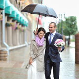Happy bride and groom walking by the rain Royalty Free Stock Images