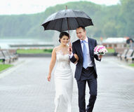 Happy bride and groom walking by the rain on their wedding day Stock Photos