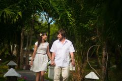 Happy bride and groom walking in the rainforest royalty free stock photo