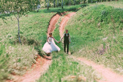 Happy bride and groom walking on road Royalty Free Stock Photos