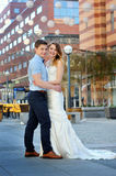 Happy bride and groom walking on a street of city Royalty Free Stock Photo