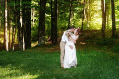 Happy bride and groom walking in the summer forest Stock Photography