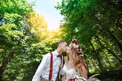 Happy bride and groom walking in the summer forest Stock Photo