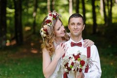 Happy bride and groom walking in the summer forest Stock Photos