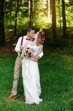 Happy bride and groom walking in the summer forest Royalty Free Stock Image