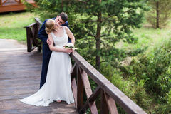 Happy bride and groom walking in the summer forest. Royalty Free Stock Image