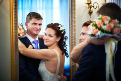 Happy bride and groom in wedding day near mirror Stock Images