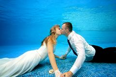 Happy bride and groom in wedding dresses kissing underwater at the bottom of the pool. Portrait. Shooting under water. Landscape orientation Royalty Free Stock Photo
