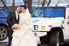Happy bride and groom about wedding limousine Royalty Free Stock Photo
