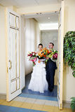 Happy bride and groom at a wedding palace doors Stock Photos