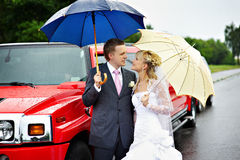 Happy bride and groom at wedding and red limo Royalty Free Stock Images