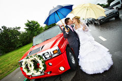 Happy bride and groom at wedding and red limo. Happy bride and groom at a wedding a walk around the red limousine Stock Images