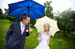 Happy bride and groom at wedding with umbrellas Royalty Free Stock Photo