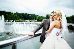 Happy bride and groom at wedding walk on bridge stock photography