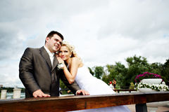 Happy bride and groom at wedding walk on bridge Royalty Free Stock Images