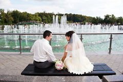 Happy bride and groom near fountain Stock Photo