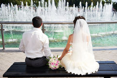 Happy bride and groom near fountain Royalty Free Stock Photos