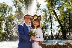 Happy bride and groom on wedding walk near fountain Stock Photos