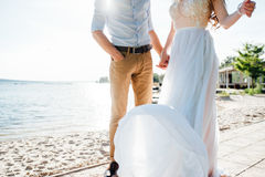Happy bride and groom on a wedding walk. Near the lake embrace. Light dress develops in the wind Royalty Free Stock Images