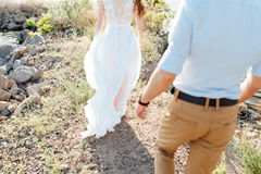 Happy bride and groom on a wedding walk. Near the lake embrace. Light dress develops in the wind Royalty Free Stock Photos
