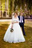 Happy bride and groom at the wedding walk. Happy newly-married couple in a park on a walk Royalty Free Stock Images