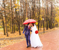 Happy Bride and groom at wedding walk with red umbrella. Autumn style concept. Happy Bride and groom at wedding walk with color umbrella. Autumn style concept Stock Image
