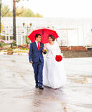 Happy Bride and groom at wedding walk with red umbrella. Autumn style concept. Happy Bride and groom at wedding walk with color umbrella. Autumn style concept Royalty Free Stock Photo