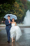 Happy Bride and groom at wedding walk white umbrella. Happy wedding couple in a rainy wedding day outdoors in park with white umbrella in rainy weather. Bride Royalty Free Stock Images