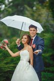 Happy Bride and groom at wedding walk white umbrella. Happy wedding couple in a rainy wedding day walking outdoors in park with white umbrella in rainy weather Stock Photo