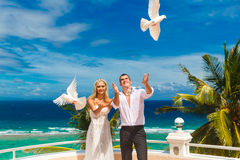 The happy bride and groom with white doves on a tropical beach u Stock Photography
