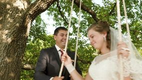 Happy bride and groom in white dress swinging on swing in summer park. swing on branch of an oak in summer forest. stock video footage