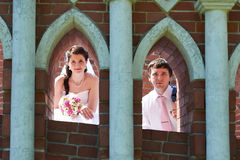 Happy bride and groom in windows of brick wall Royalty Free Stock Photography