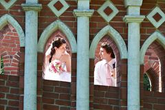 Happy bride and groom in windows of brick wall Royalty Free Stock Photos