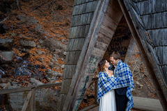 Happy bride and groom wrapped in blanket softly hugs on the wooden bridge at mountains. Autumn forest background. Happy bride and groom softly hugs on the wooden Stock Images