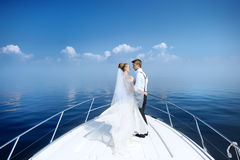 Happy bride and groom on a yacht royalty free stock photography