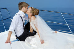 Happy bride and groom on a yacht Stock Photos