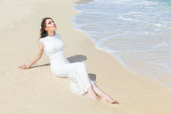 Happy bride having fun on a tropical beach. Wedding and honeymoo Royalty Free Stock Images