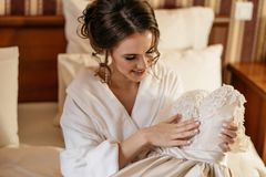 Happy bride holding her wedding dress and smiling. Wedding morning Royalty Free Stock Photos