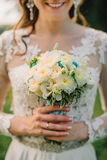 Happy bride holds a wedding bouquet of white roses Stock Photos