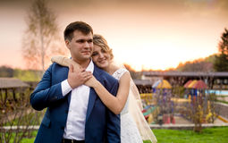 Happy bride hugging groom from back at beautiful sunset Royalty Free Stock Image