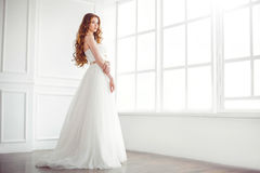 Happy bride indoors. Wedding. Beautiful bride indoors at big window in full lenght looking away. Side view Stock Photography