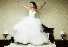 Happy bride jump on bed. Royalty Free Stock Photos