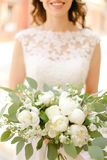 Happy bride keeping bouquet of flowers and wearing white dress. royalty free stock images